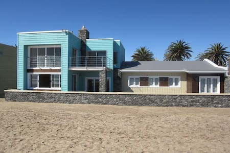 Situated right on the beach in the town centre, this family seaside house affords you unspoiled views of the sea,direct access to the beach and beautiful sunsets behind the  Swakopmund Jetty. Popular restaurants and Tourism spots are within walking distance of the house.