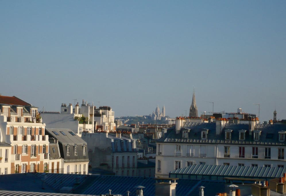 View from the two windows : roofs of Paris and Montmartre Sacré-Coeur basilica...