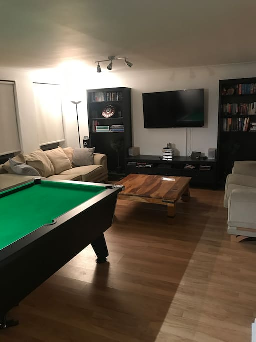 "Main living area with pool table, large coffee table, 57 "" TV, and seating for 5/6 people on the couches."