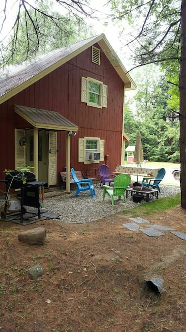 Outdoor area with gas grill, picnic table and a fire pit.