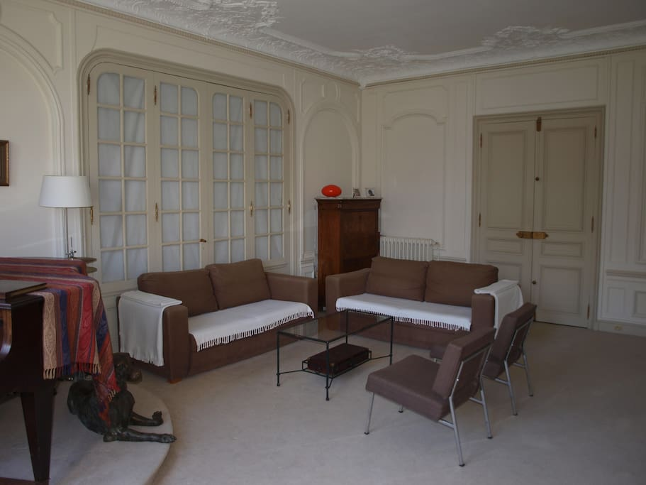 The living room, bright and spacious with a piano and confortable couches.