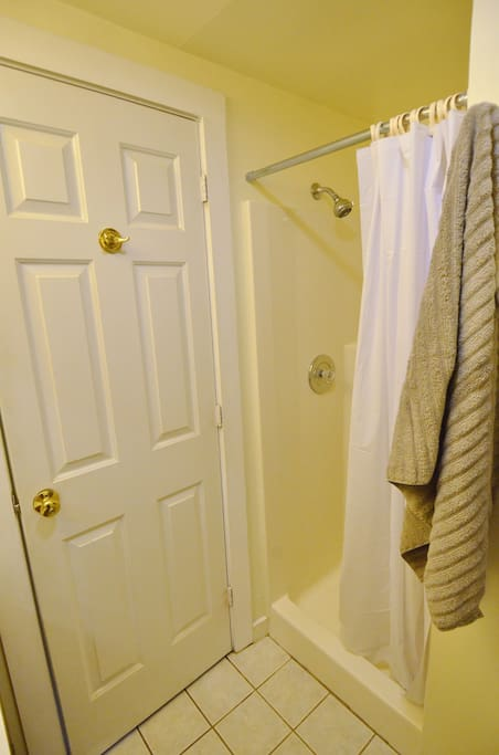 Stand up shower with linens.