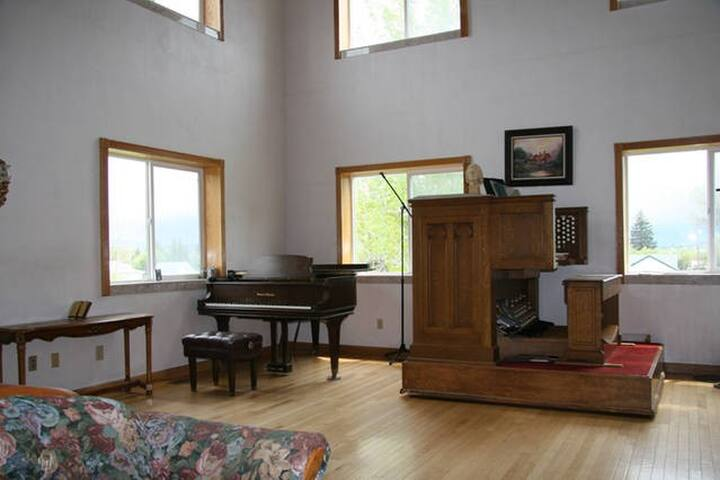 Grand piano and pipe organ in front room.