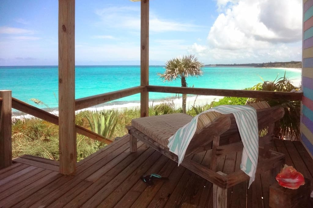 Relax on your oceanfront deck looking at the turquoise water waiting for you!  Two colorful chaise lounges await you on the pink sand as well!