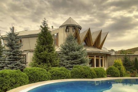Дом с уникальной архитектурой у подножия гор.