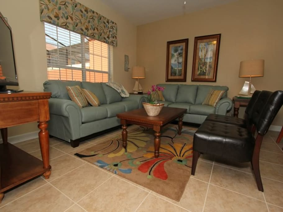This is the living room on the first floor of the home looking out to the pool.