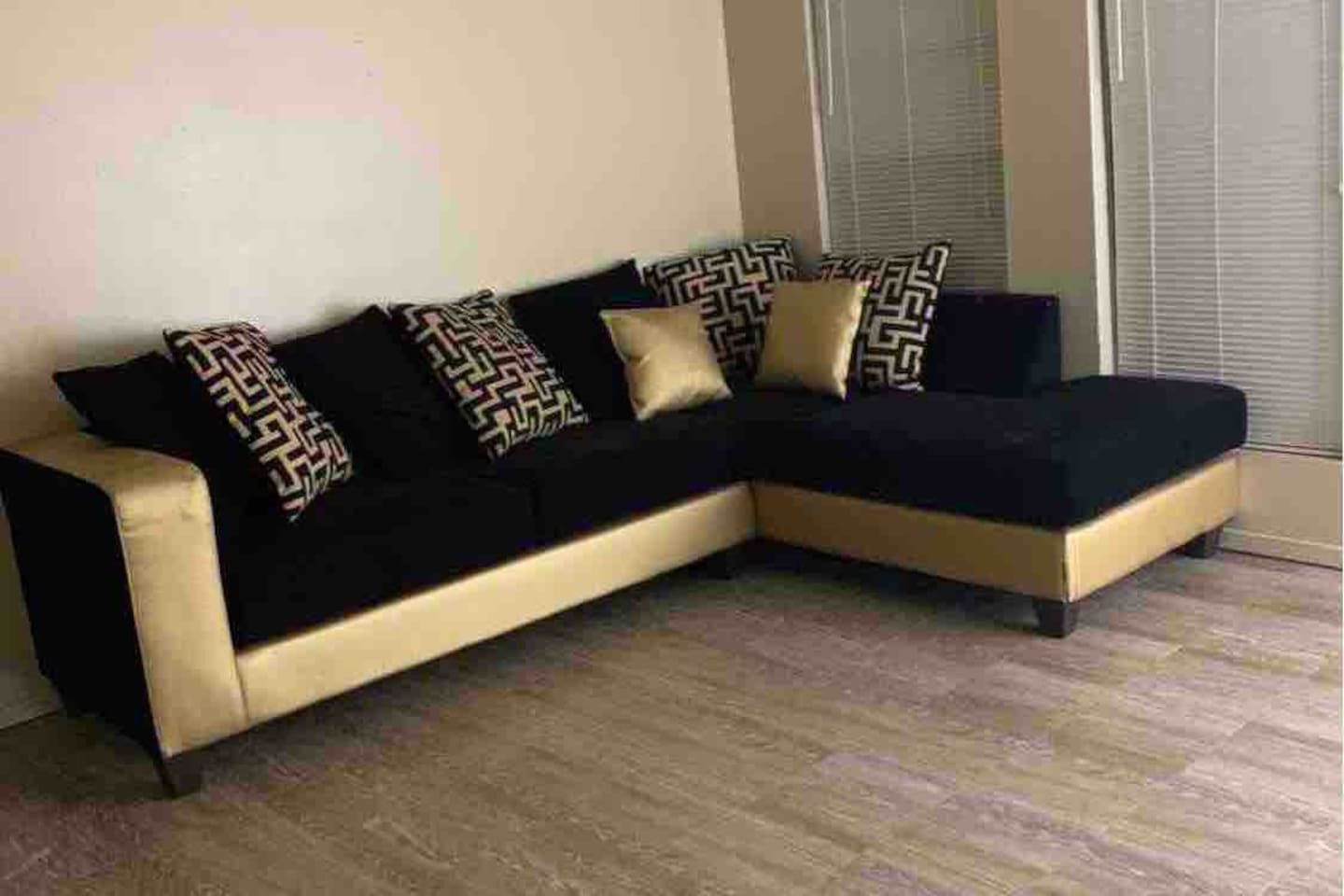 Sectional black and gold designed couch, perfect for guest sitting.