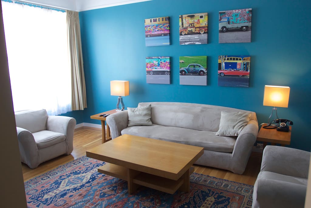 Bright living room with comfy couch and armchairs.