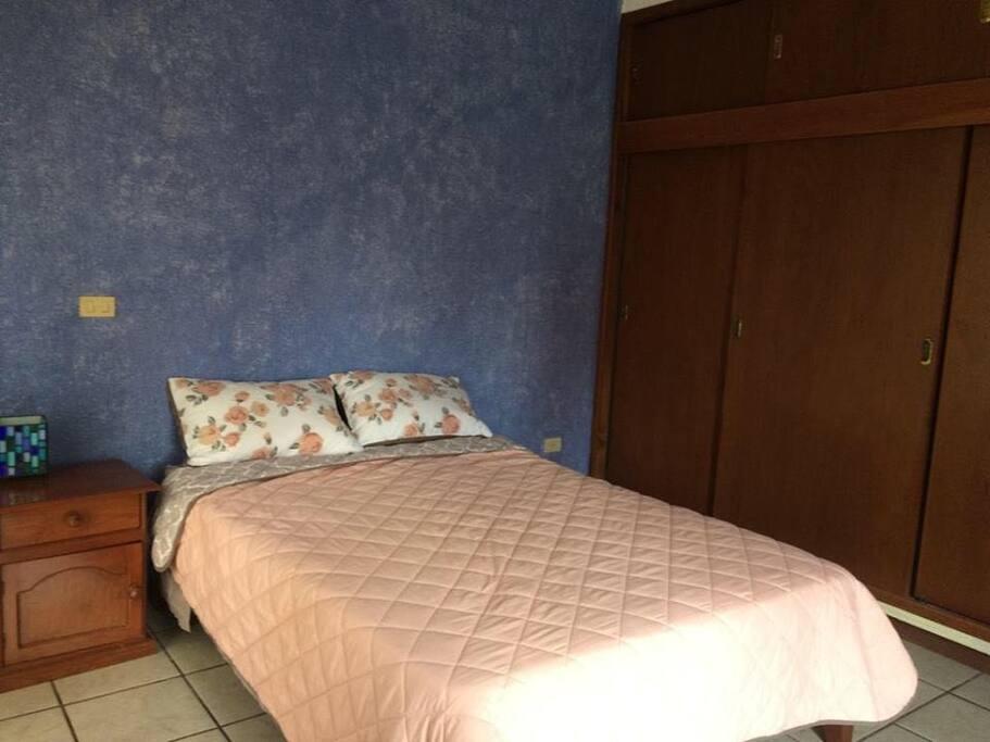 Recámara uno, con una cama matrimonial, closet y balcones que permiten mucha luz y ventilación