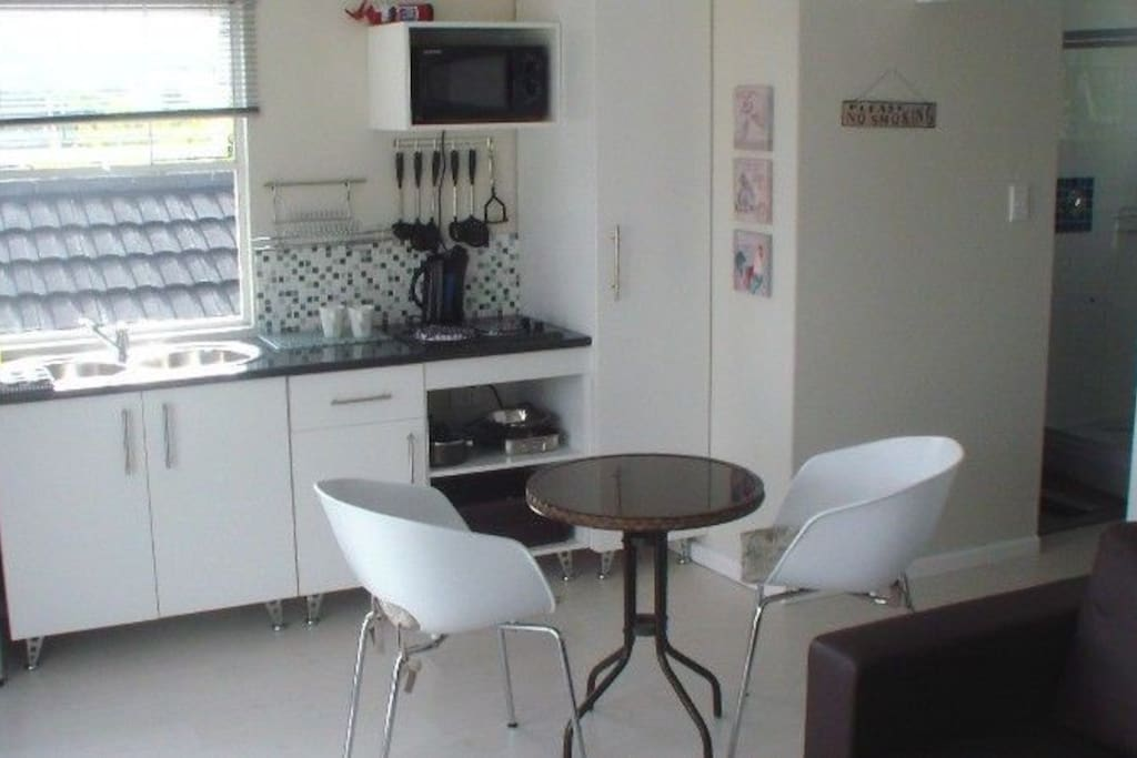 Fully equipped kitchenette with table and chairs.