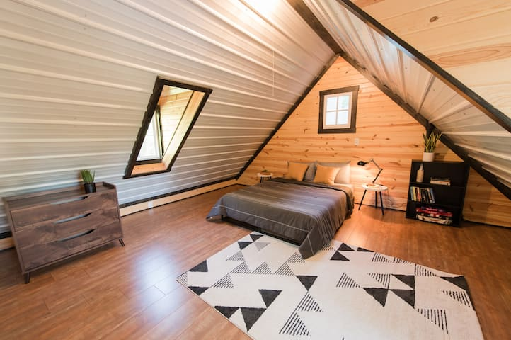 The loft, accessible via a spiral staircase. The loft features a queen bed, chest of drawers, and seating.   The windows and dormers provide the space with tons of natural light and an excellent view of the water.