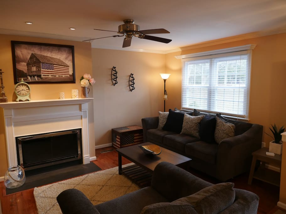 """Living Room with 55"""" HDTV and working wood-burning fire place."""