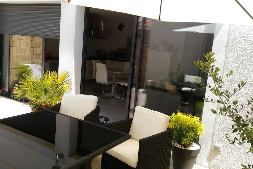 Terrasse spacieuse et végétalisée, prévue pour des repas en extérieur