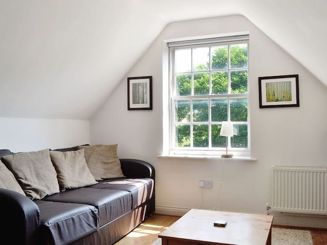 The upstairs is one room with the bed at one end and seating area at the other.
