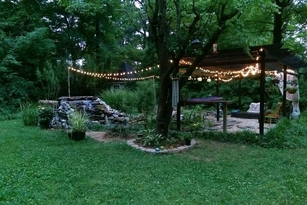 Sitting area in the back yard w/fire pit lighting at pond