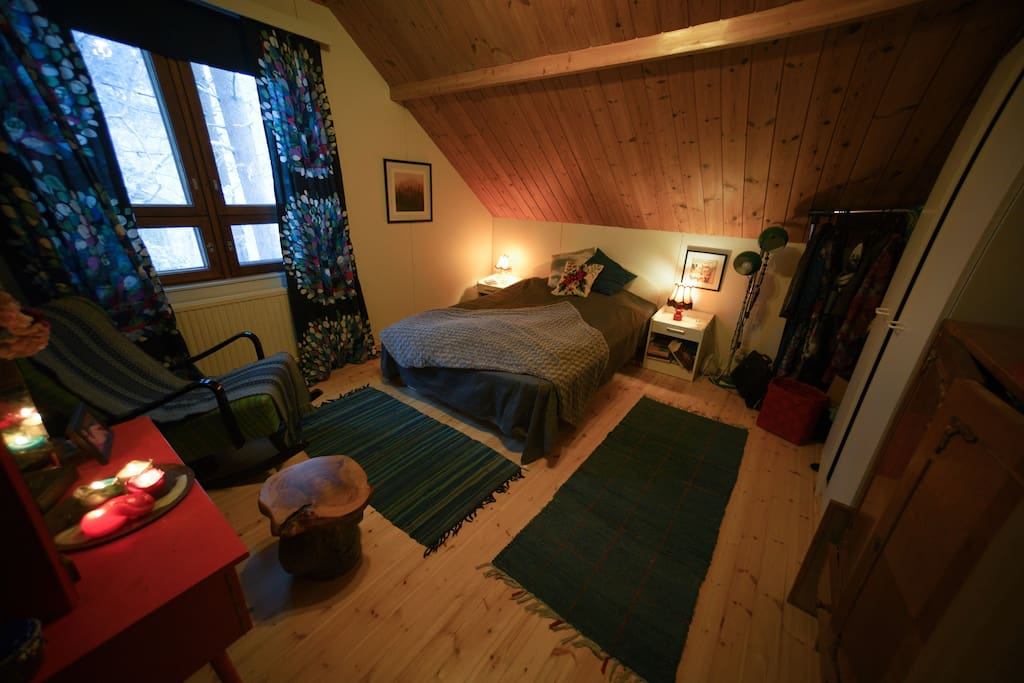 Cozy, retro spirited bedroom upstairs with pine wood floor and ceiling panels.
