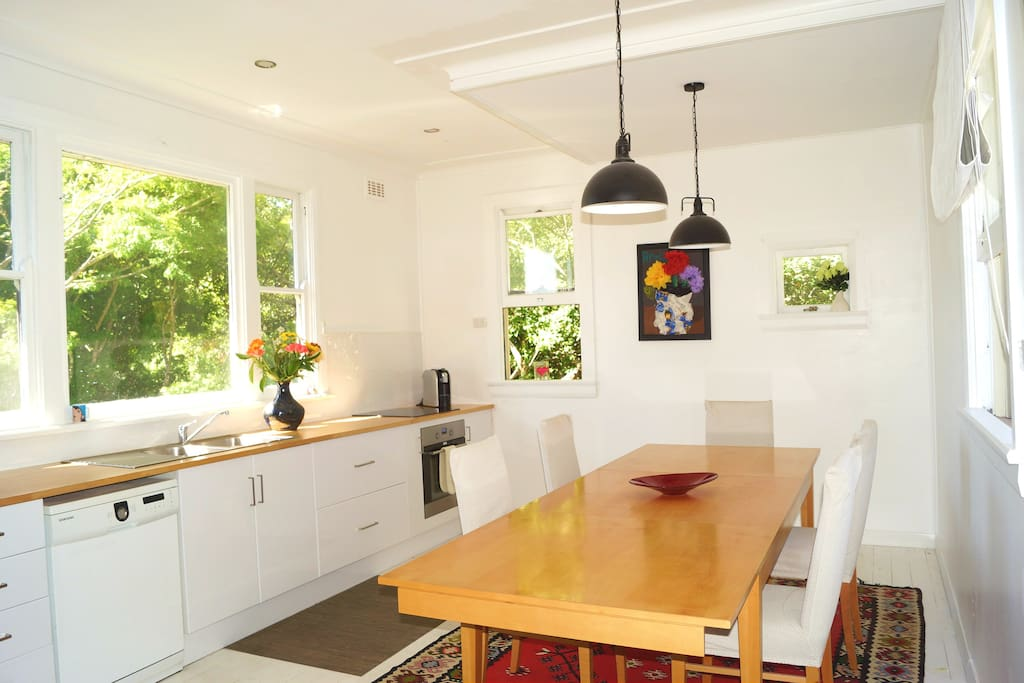 spacious and airy white kitchen with massive table and 6 dining chairs