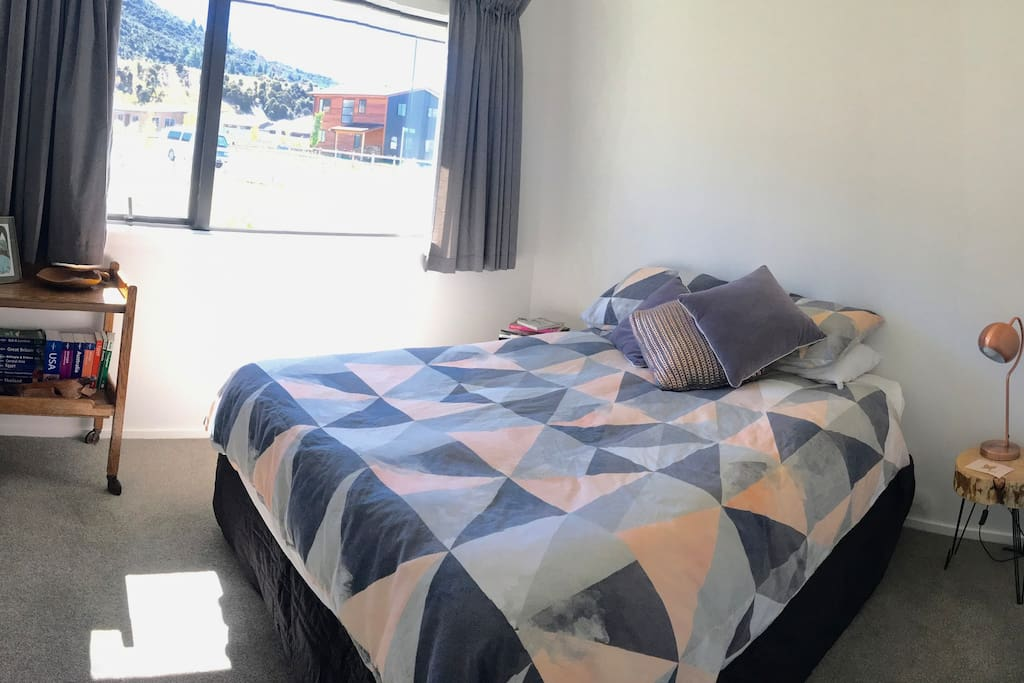 Clean, sunny, modern bedroom with a comfortable queen sized bed.