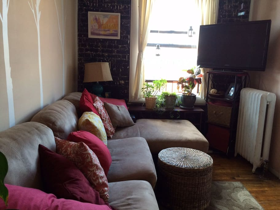Living room equipped with TV, window has great view of Manhattan sklyine to the West