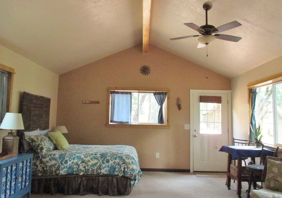 Open floor plan and vaulted ceiling with wood beam adds spaciousness to room.