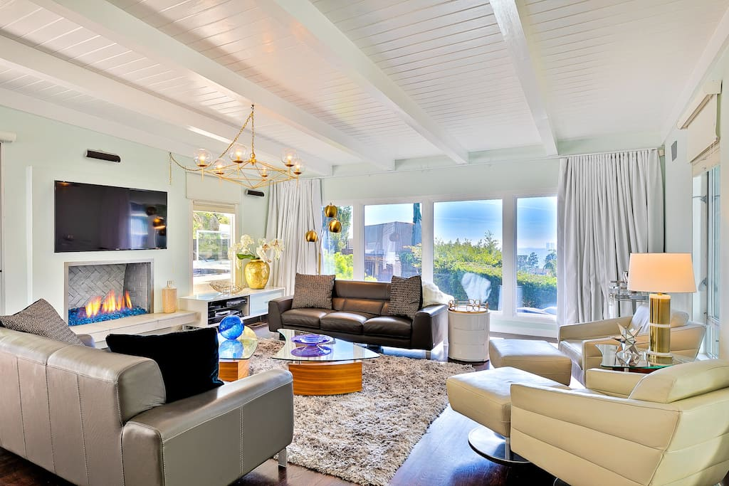 Fresh and Inviting living room with white beadboard ceilings and white beam beckons you to sit and relax. Windows provide a background of amazing Hollywood Skyline views.