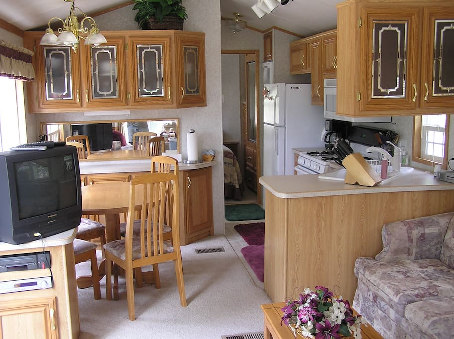 The kitchen has a full refrigerator, Propane stove and double sink with dining area.