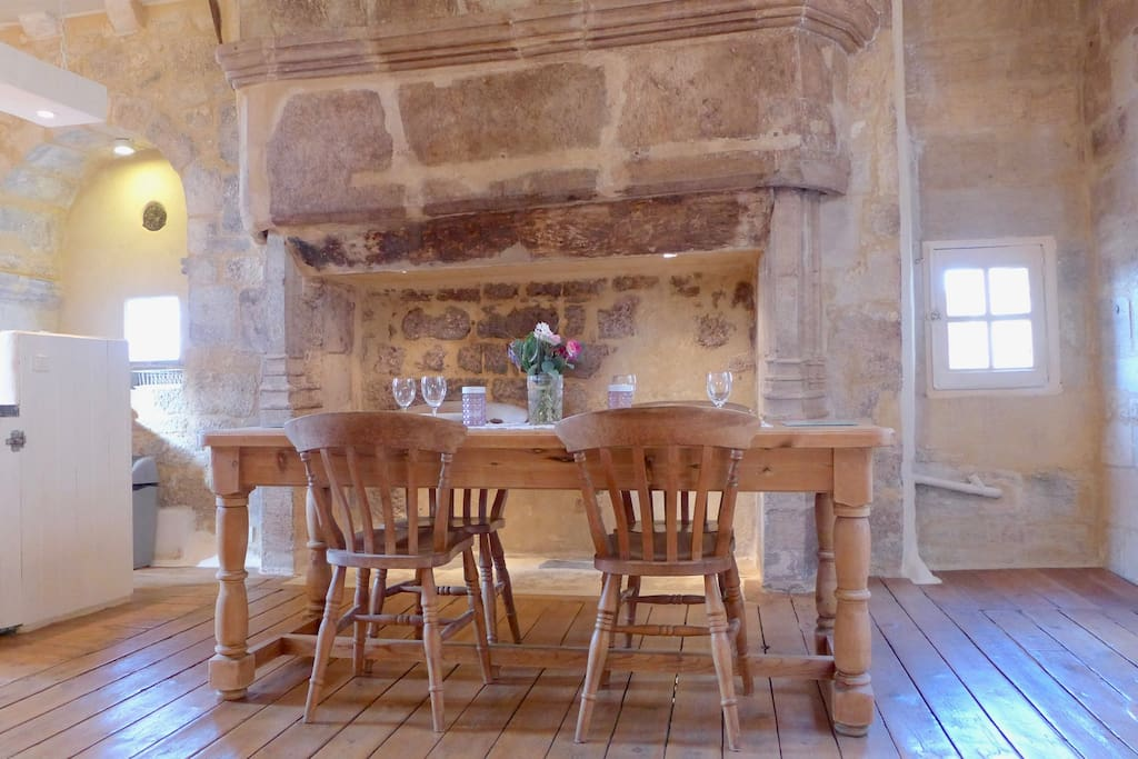 Dining table in front of the 13th Century fireplace.