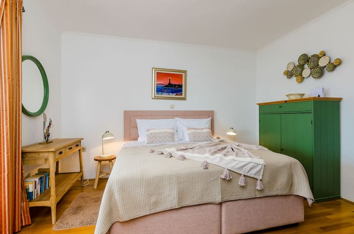The recently redecorated bedroom features a high quality boxspring bed and a set of new furniture and accessories.