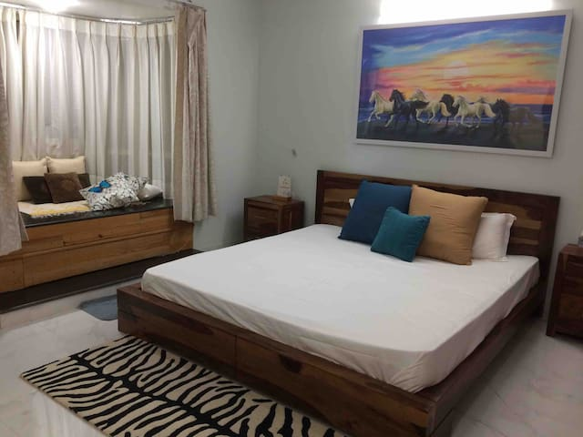 Master bedroom with king-sized bed and  a sofa in addition which can be turned into Queen sized bed ,a bay window overlooking lush green park, a very convenient  work space