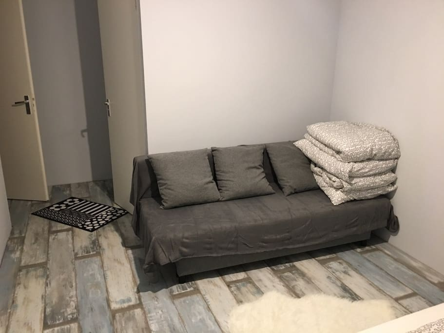 a sofa in the bedroom which can be converted into a bed for two