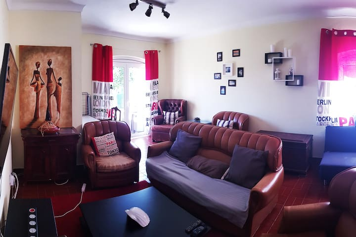 First part of the cozy living-room with garden access, flat screen and sofas to relax.