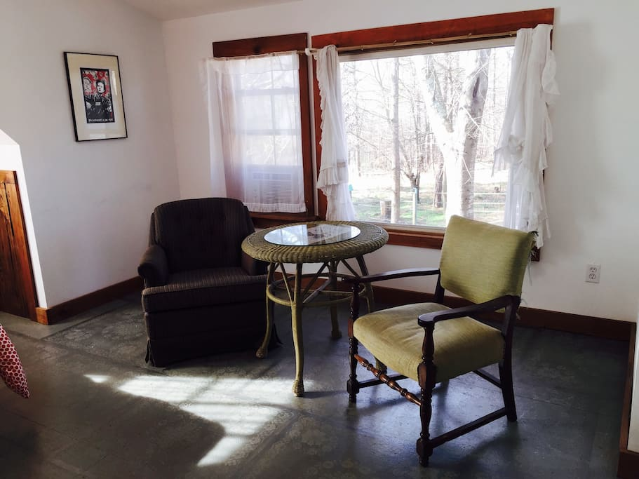 The room has a seating area with a pasture view.