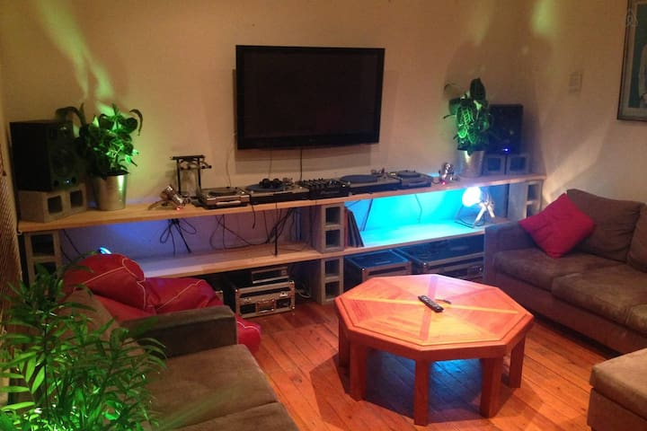 Living room with indoor plants, Chromecast TV, vinyl's, CDJ's and mixer.