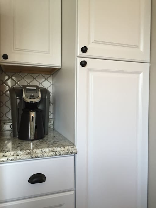 Keurig 2.0 coffee maker and supplies in the cabinet above!