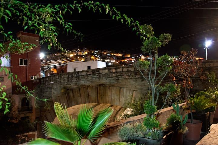 Vista nocturna al puente y la ciudad desde la terraza común