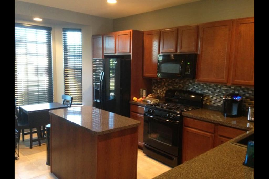 The kitchen has a breakfast bar, an island, and features modern finishes.