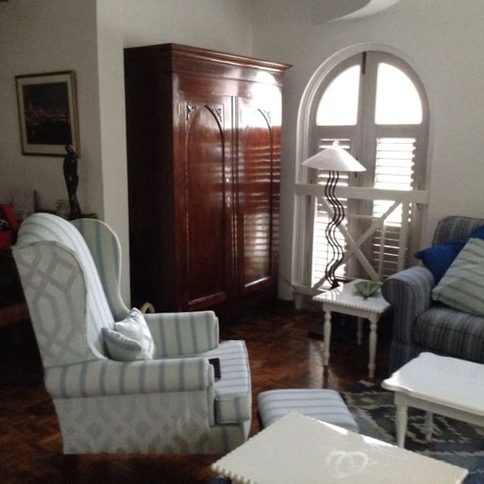Coastal style living room  with screened louvered windows and and a great vie of Ocho Rios