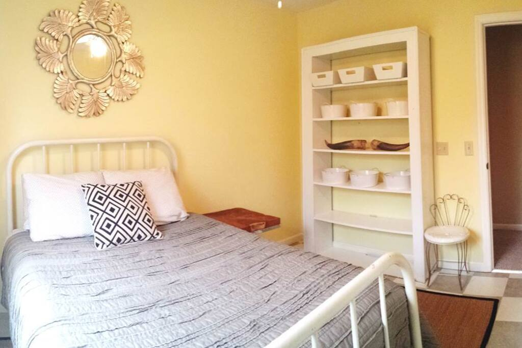 Yellow Guest Bedroom with Double Bed, Spacious Closet with Full Length Mirror, and a large shelving unit to store your clothes.