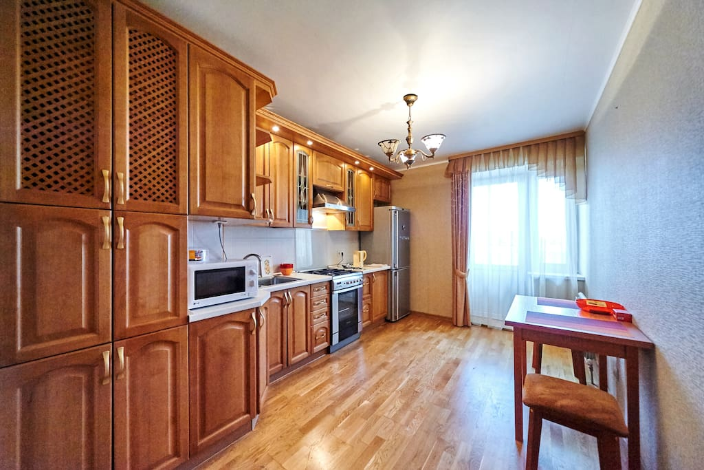 Микроволновая печь, духовой шкаф, плита, холодильник, чистая посуда и кастрюли для приготовления пищи.