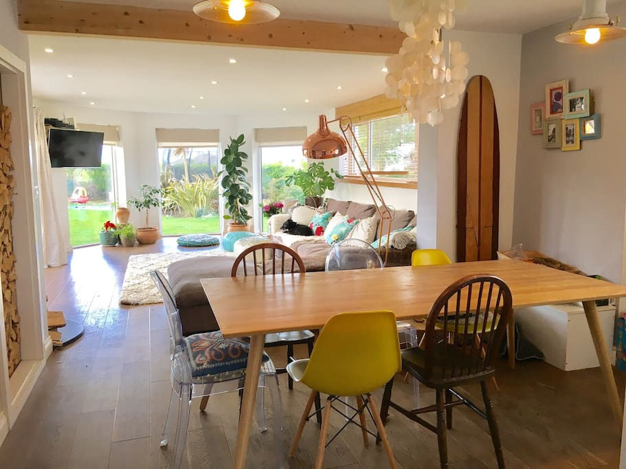 This large open plan living dining area is a delightful sun trap with distant sea views epic sunsets and where the barriers between indoor and out can merge