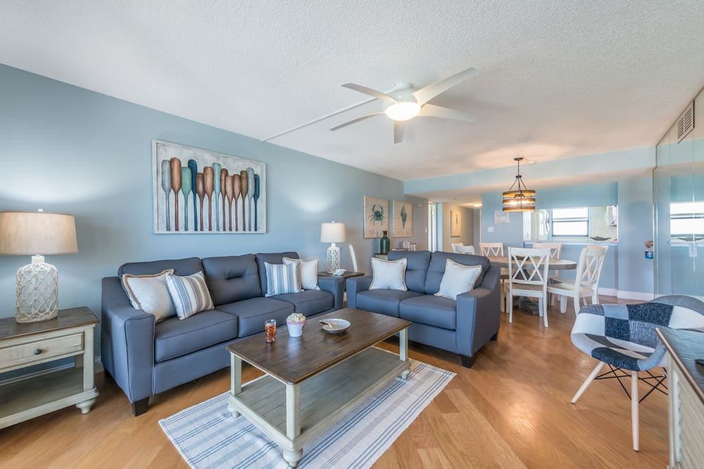 "Spacious living & dining room with direct ocean views. Queen sofa sleeper & 65"" TV"