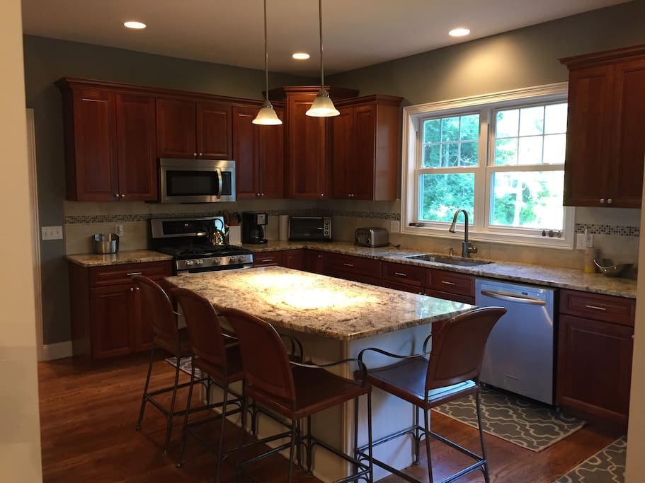 cherry kitchen with hardwood floors and granite countertops