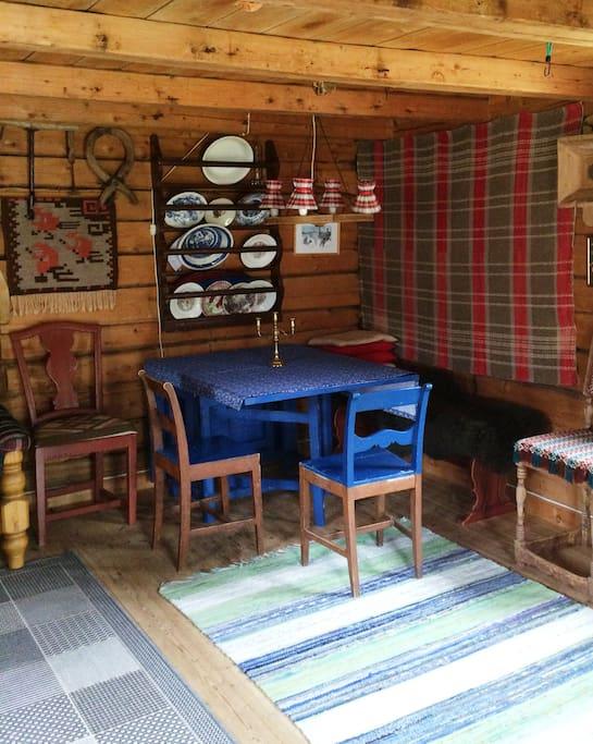 Spisekrok med tremøbler og filleryer på gulvet. Du kan lage mat på det lille kjøkkenet, eller bestille enkel frokost mot tillegg i prisen.