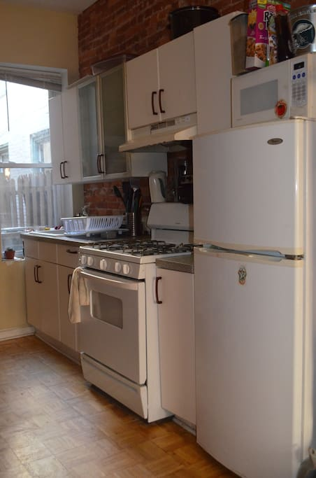 Kitchen including: gas oven, refrigerator, coffee maker, and sink.