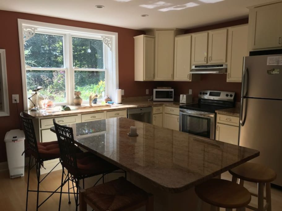 Sunny full kitchen has large  breakfast bar plus dining table for six.