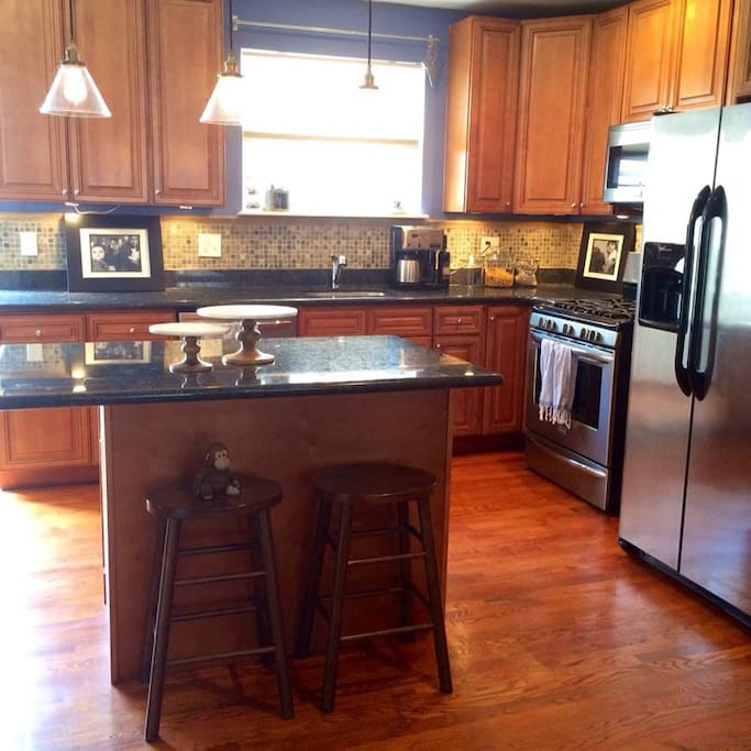 Kitchen with gas range, dishwasher, microwave, ice maker and auto coffee maker.