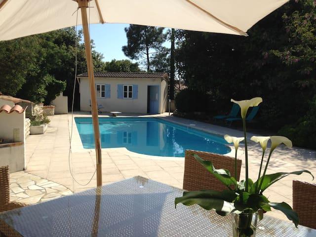 Dans un jardin arboré, belle maison avec piscine.