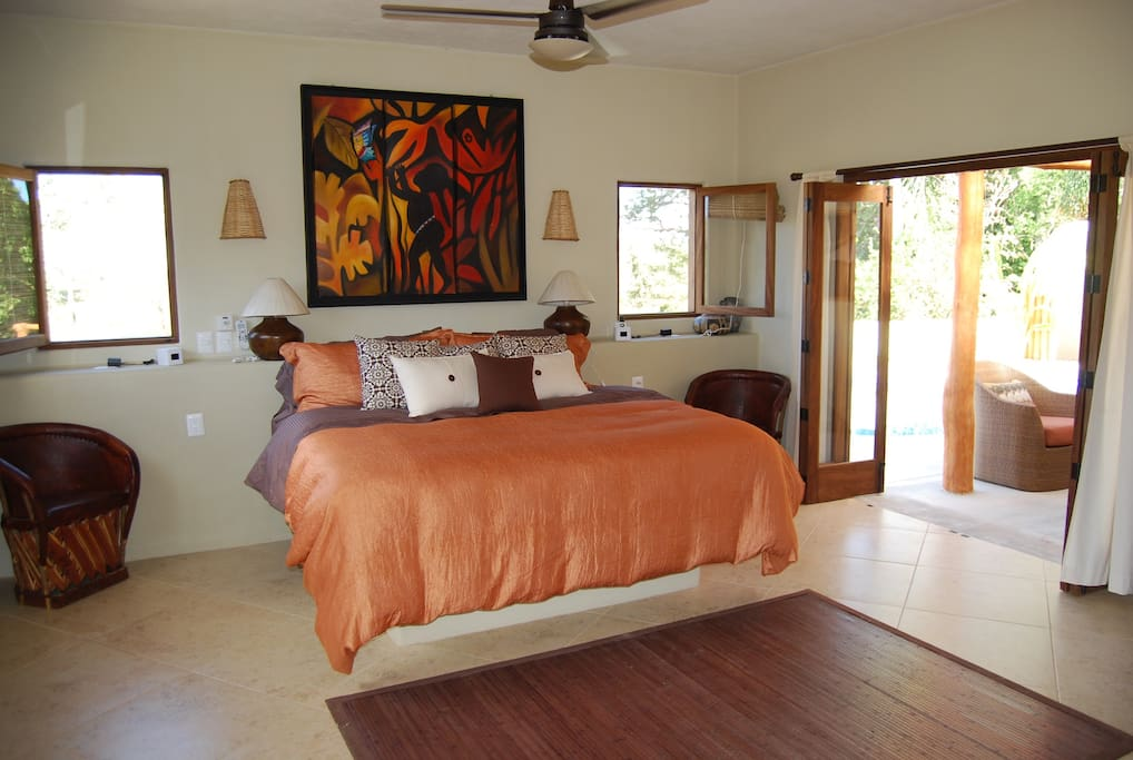 Tastefully appointed master bedroom with king bed, cozy linens, private bath and French doors with pool deck access.