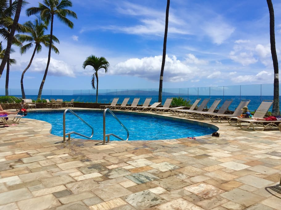 Heated oceanfront pool with spacious patio, lounge chairs, and tables