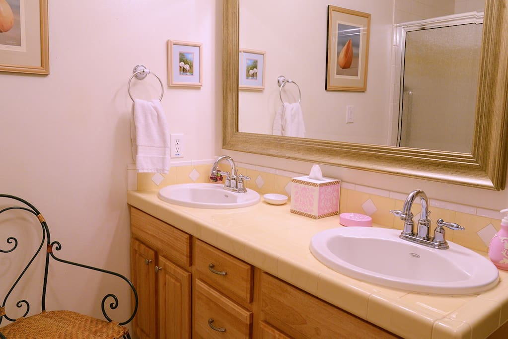Large bathroom with double sinks and walk in shower with private toilet area.